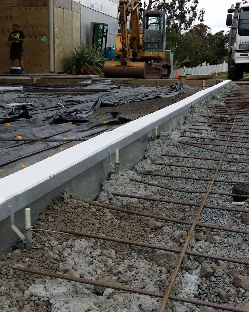 Polystyrene insert to assist screeing and prevent wet concrete ingress into channel